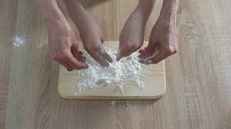 panelas : Hands of grandmother and granddaughter pouring flour on plank, cooking time