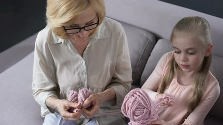 breiwerk : Blond grandmother knitting with her little granddaughter at home, handmade