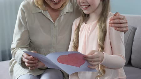 two hearts : Smiling granddaughter gifting handmade greeting card with heart to grandmom Stock Footage