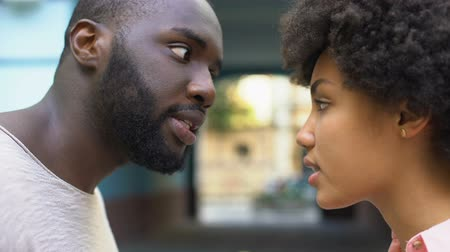 agressivo : Young afro-american couple arguing outdoor, misunderstanding, jealous spouse