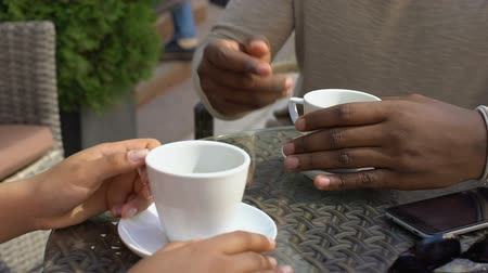 kafeterya : Black man talking to woman sitting in cafe, colleagues drinking coffee together