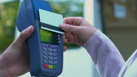 card pin : Woman puts card to payment terminal and takes parcel after successful payment Stock Footage