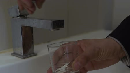 drinking water supply : No water coming from tap, man trying to drink, bad service in cheap motel Stock Footage