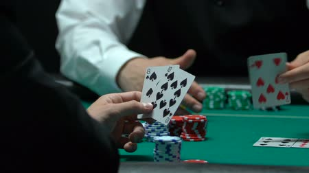 croupier : Poker player has cards for ten-high straight, making bigger bets. Stock Footage