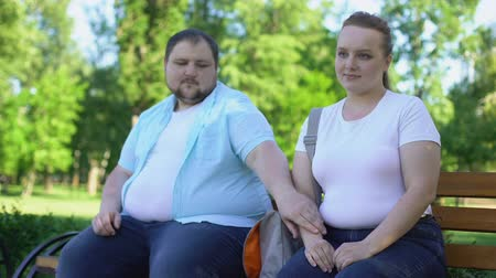 fondness : Obese couple on first date, man tenderly taking girlfriend hand, love and care