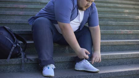libras : Hard for fat young man to tie shoelaces, challenges obese people face every day