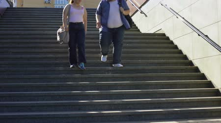 понимание : Obese couple walking on stairs, happy together, acceptance of person as he is