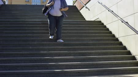 diyabet : Fat male student walking downstairs, problems of overweight among young people