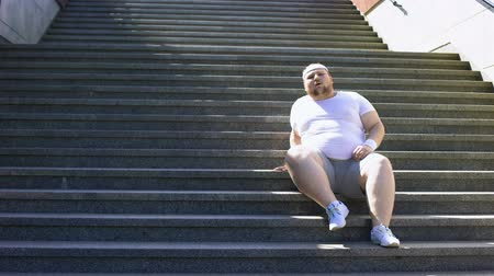 desperate : Obese man sitting down on stairs to rest for minute, exhausted after workouts