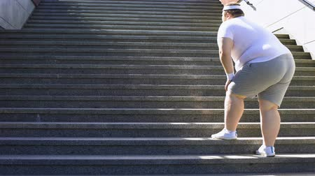 osteoarthritis : Obese man climbing stairs, overweight causes pain in joints, varicose veins