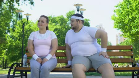 bescheiden : Fat young man acquainting with pretty obese lady sitting in park, confidence