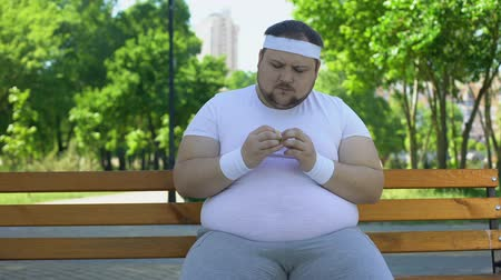 glicose : Fat man admiring burger in park, addiction to junk food, unhealthy lifestyle