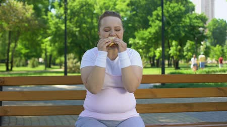 cholesterol : Fat girl struggles with temptation to eat burger, prefer junk food, no willpower Stock Footage