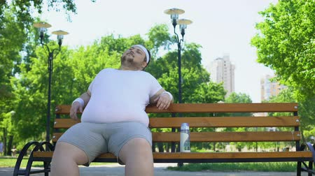 overcome : Confident fat man sitting in park, feels happy, contented with life, self-love