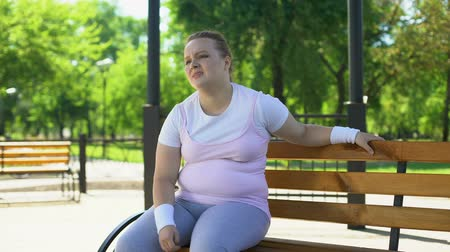 упитанность : Obese woman exhausted after strenuous workouts outdoors, minute rest on bench Стоковые видеозаписи