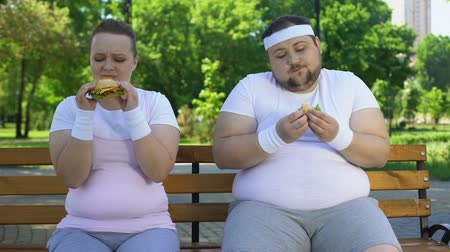 диета : Fat young couple eating hamburgers, addicted to junk food, lack of willpower