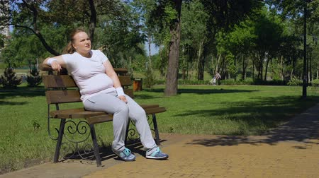 bodyweight : Fat girl sitting on bench, tired after jogging but goes on running, motivation Stock Footage