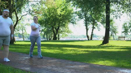 пухлый : Joyful chubby girl outrunning obese man tired after jogging, exhausting workouts