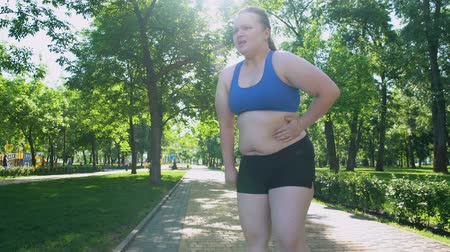 willpower : Obese girl jogging, suffocating, feels belly pain after tiresome workouts