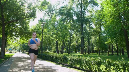 пухлый : Pretty obese girl jogging and smiling, self-confident motivated person training Стоковые видеозаписи