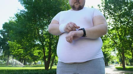 heart rate : Obese man monitoring heart beat on smartwatch after jogging, app for healthcare