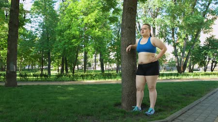 willpower : Obese girl tired after jogging, leaning on tree, tiresome workouts outdoors