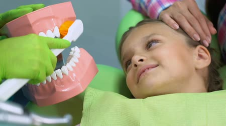 зубная боль : Stomatologist teaching small patient to brush teeth properly, dental care