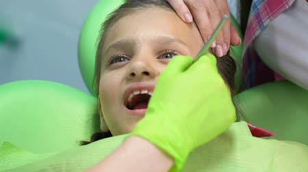 dětinský : Mother comforting scared little girl during dental examination.
