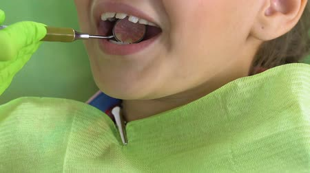 inspection : Excited kid sitting in dental chair, doctor examining teeth with special mirror