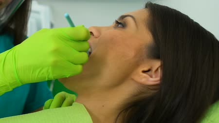 proteza : Dentist examining woman teeth through mouth mirror, lady satisfied with results