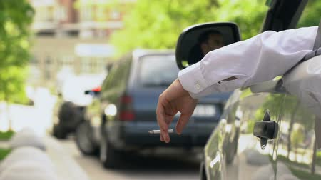 koçan : Man smoking in auto, dumping cigarette ash on street, stuck in traffic jam Stok Video