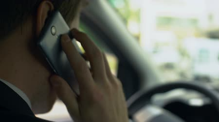 unsuccessful : Man nervously talking on cell phone in car, upset over failure, tough day Stock Footage