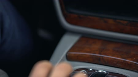 freio : Man shifting gear, automatic transmission, luxury car with wooden interior