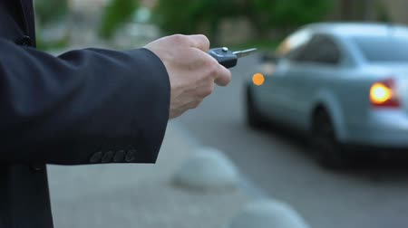auto parking : Man turns on car alarm, security concept, risk of hijacking car parked on street Stock Footage