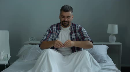 uzun ömürlü : Man in bed taking biologically active additives, feeling himself full of energy
