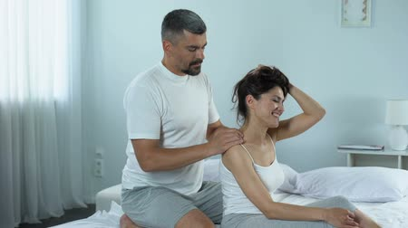 meghittség : Handsome man kneading his girlfriend shoulders, gentle and relaxing massage Stock mozgókép