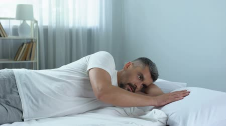 night life : Sad handsome man gently stroking pillow next to him, loneliness after divorce