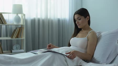 газета : Beautiful woman reading glossy magazine with interest, pleasant pastime at home