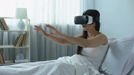 plunging : Girl in vr headset plunging into amazing world of virtual reality from home bed