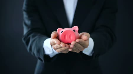 skarbonka : Businessman holding piggybank in hands, company investment, financial consultant Wideo