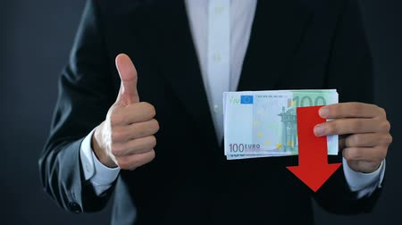euro banknotes : Financial expert holding euro banknotes, showing thumbs up and down, falling