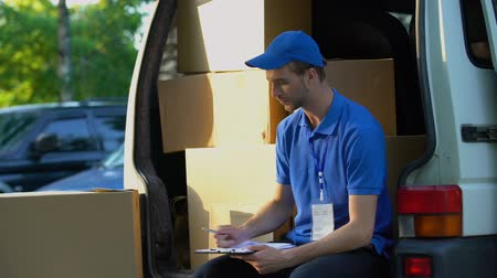 szállító : Young deliveryman writing parcel distribution report and smiling, sitting in van