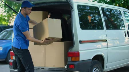 mozgás : Courier taking boxes out from delivery van, moving company, goods shipment Stock mozgókép
