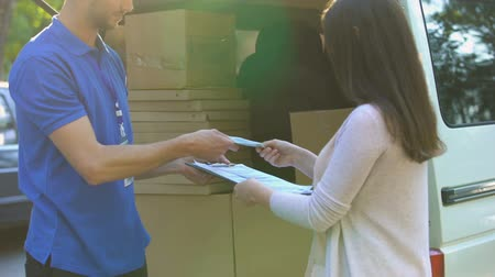 квитанция : Mailman receiving parcel from female and giving receipt, international shipping Стоковые видеозаписи