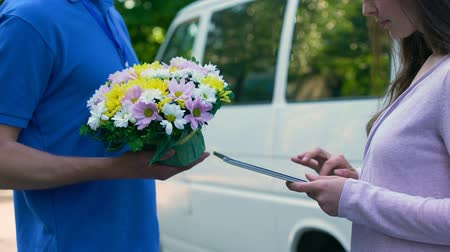почтальон : Courier delivering flowers woman, tablet signature, birthday present family care Стоковые видеозаписи