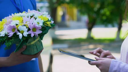 почтальон : Delivery company client appending signature on tablet and receiving flowers