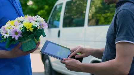 почтальон : Man appending signature on tablet and receiving flower present from delivery man