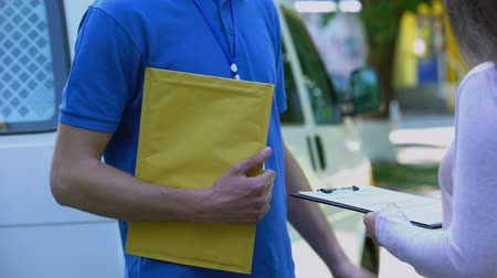 почтальон : Woman signing proof delivery form and receiving yellow package from courier Стоковые видеозаписи