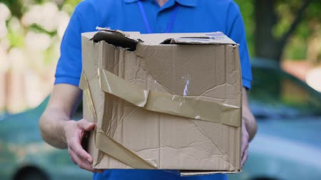 poczta : Male courier showing damaged box, cheap parcel delivery, poor shipment quality