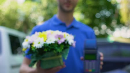 florescente : Flowers delivery worker holding bouquet and payment terminal, customer care Stock Footage